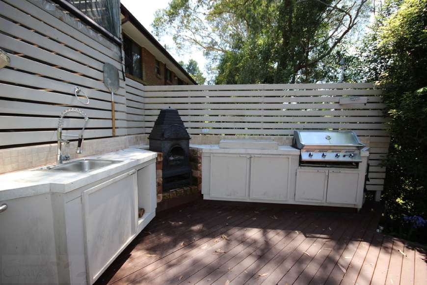 Outdoor kitchen with woodfire pizza oven and large BBQ